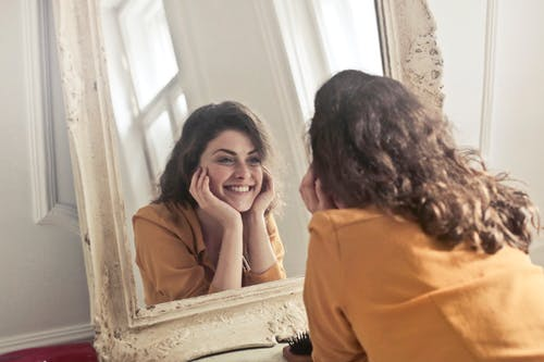 """A woman looking in the mirror wondering, """"How can personal development help me?"""""""